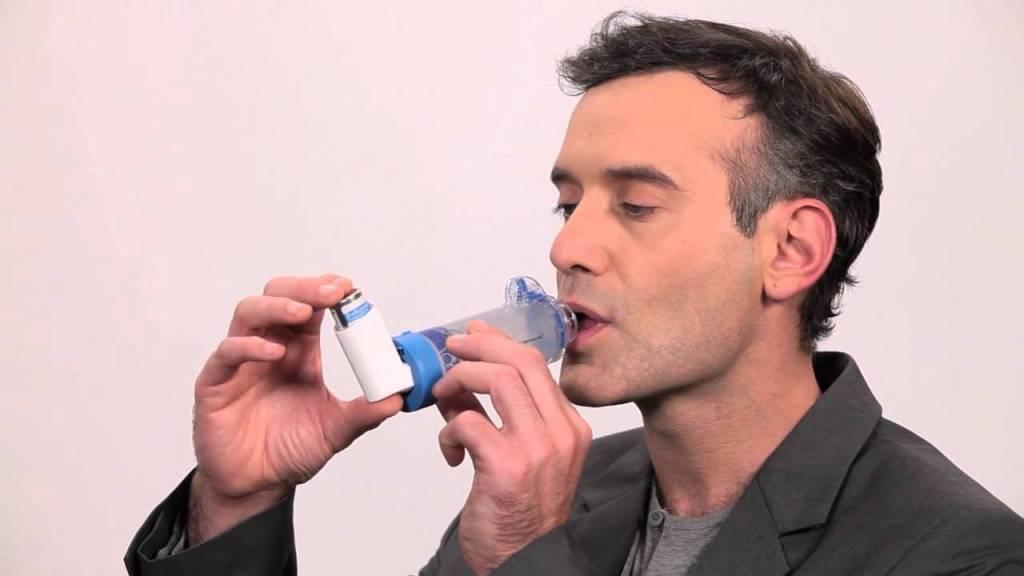 Hombre utilizando un inhalador en el tratamiento del asma